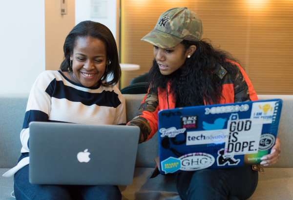 Two black women sit on a couch, with laptops on their lap. One woman is pointing to the other woman's laptop screen. The other woman is smiling. Photo is cc-by 2.0 WOCinTech Chat